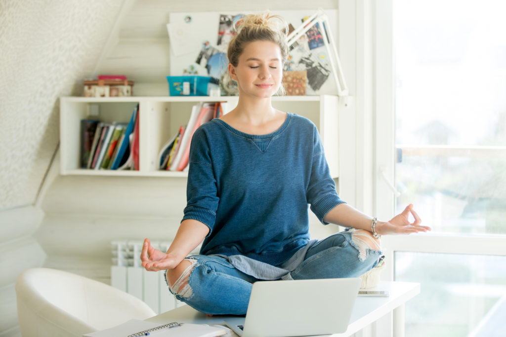 Femme en méditation assise sur un bureau bien rangé