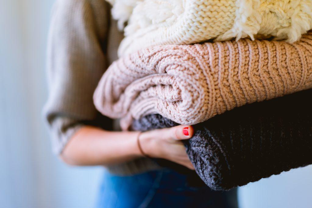 femme portant une pile de pulls