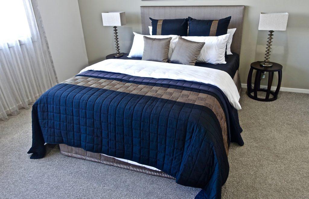 lit double avec deux tables de chevet symétriques, couvre-lit bleu marine et beige