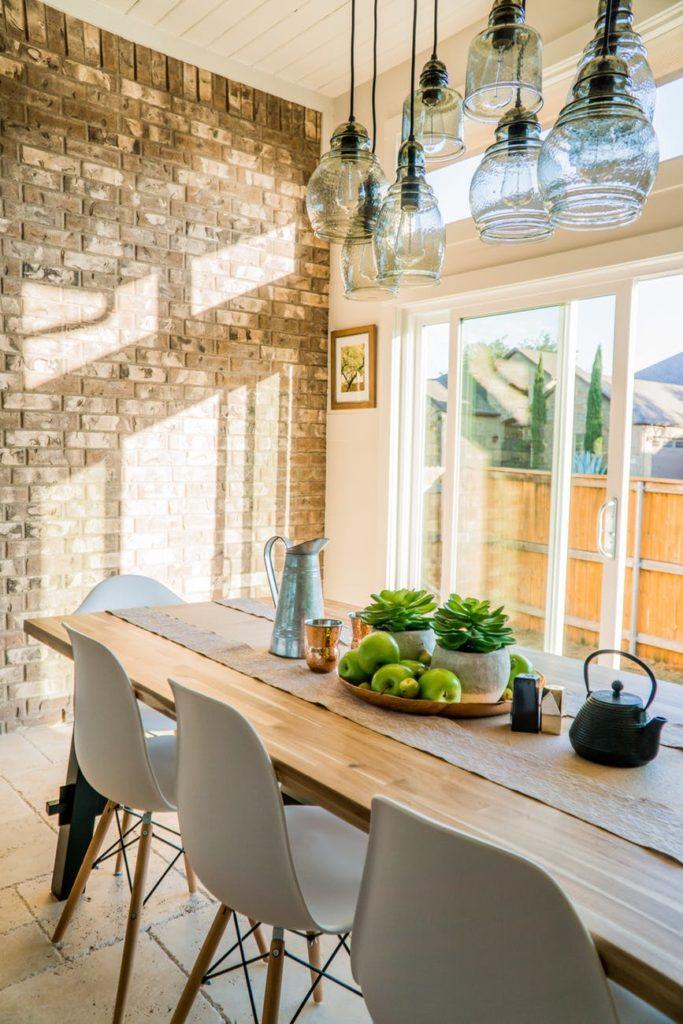 Table de salle-à-manger en bois, avec chaises blanches et luminaires en verre