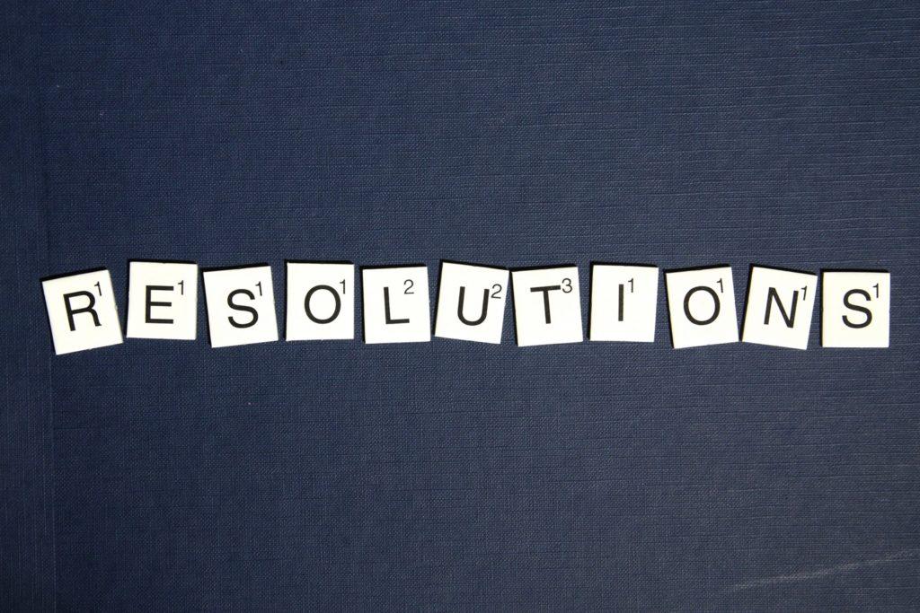 """""""Résolutions"""" écrit avec des lettres de scrabble sur fond noir"""