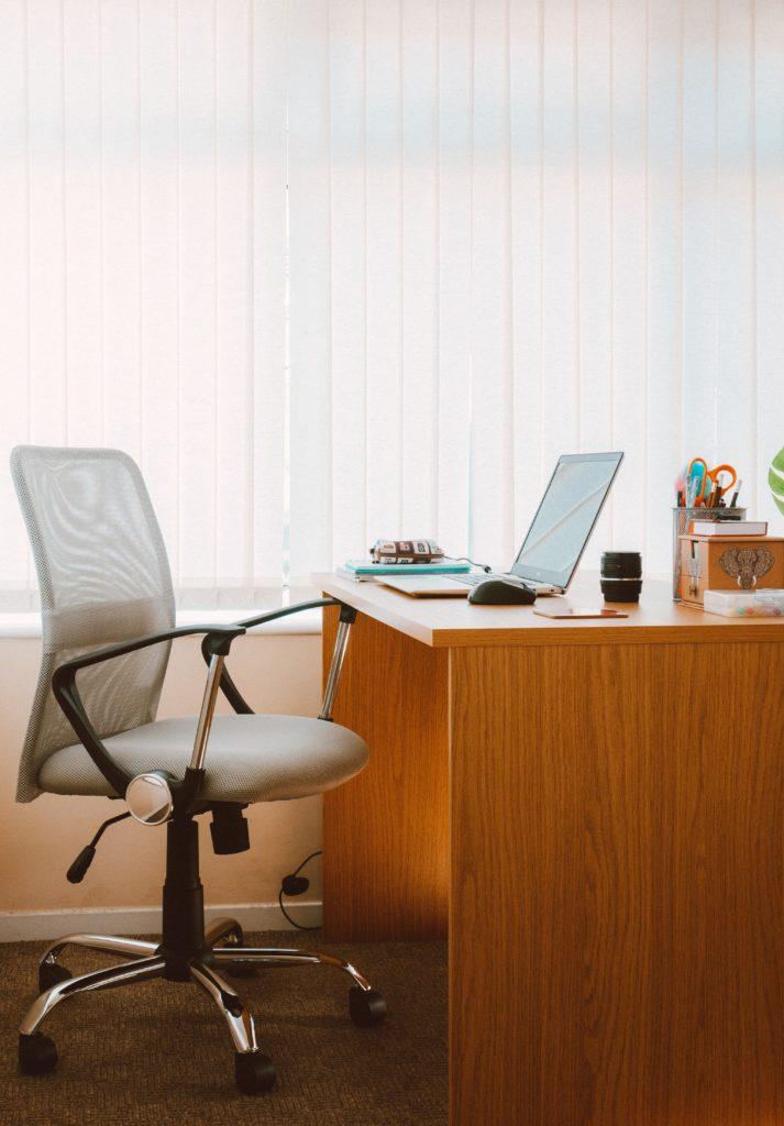 Bureau en bois avec un ordinateur portable, et chaise de bureau gris clair