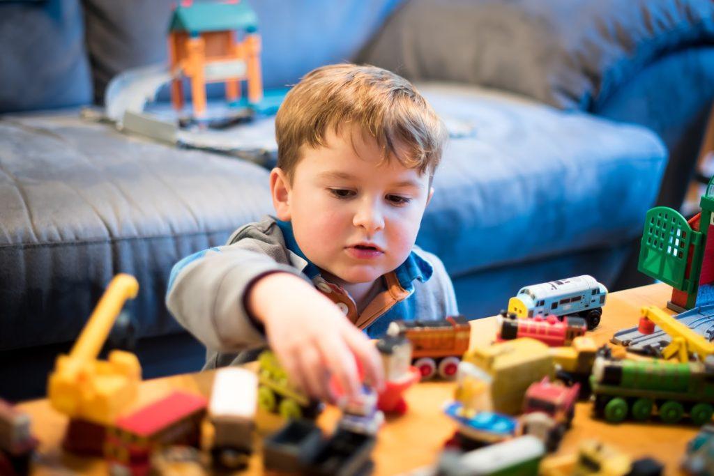 Jeune garçon jouant avec des petites voitures