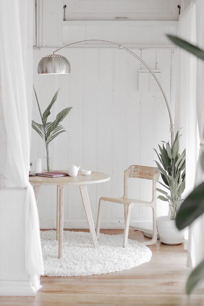 table ronde et chaise en bois et lampadaire métallique
